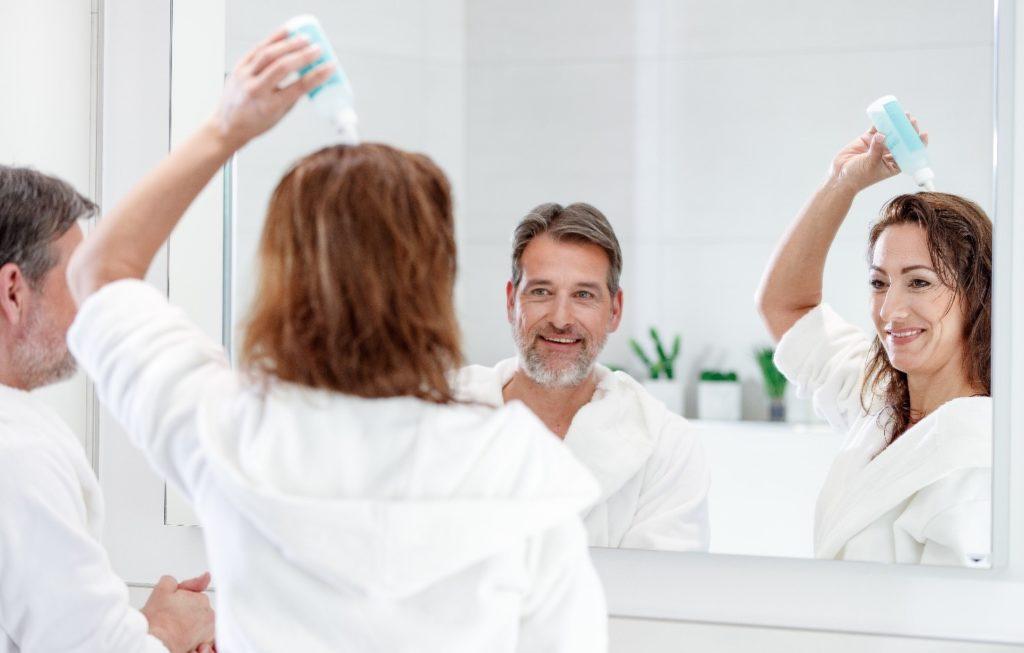 Mann und Frau wenden Haarpflege an