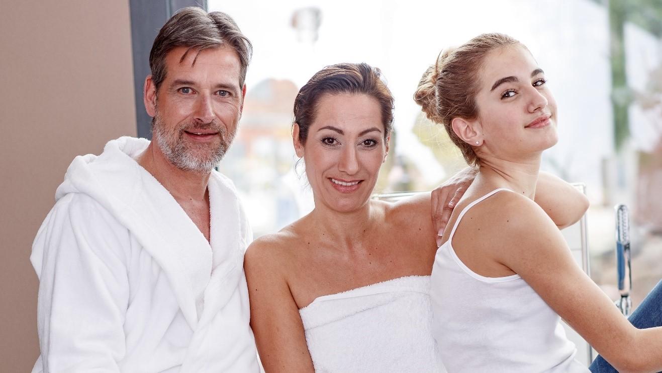 Mann, Frau und Tochter tragen Bademäntel
