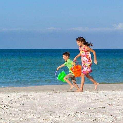 Kinder rennen an einem Sandstrand