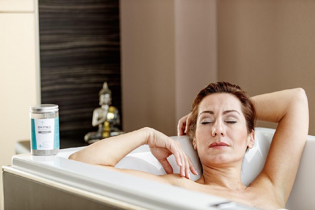 Frau entspannt in einer Badewanne mit Fango Badesalz